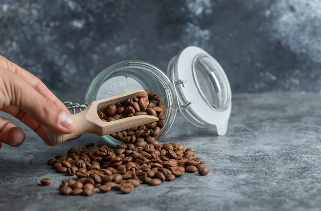Male hand holding wooden spoon of coffee beans on marble background