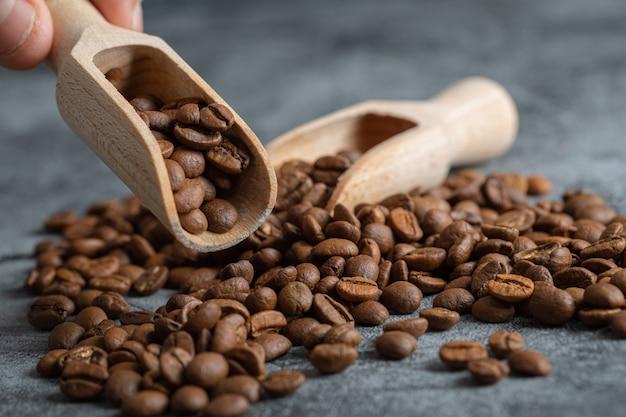 大理石の背景に芳香のコーヒー豆の木のスプーンを持っている男性の手