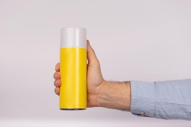 白い背景の上の黄色のバルーンボトルを持っている男性の手。閉じる。モックアップ。