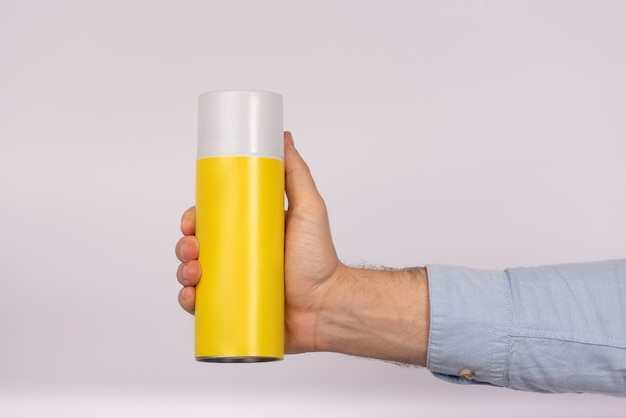 Male hand holding yellow balloon bottle on white background. close up. mock up.