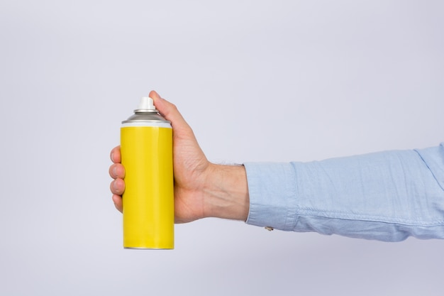 Male hand holding yellow spray bottle on white wall. copy space, mock up. side view