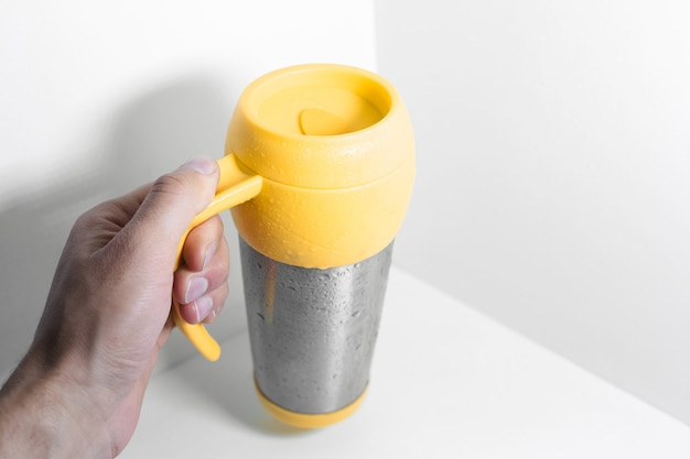 Male hand holding yellow steel thermo mug on white.