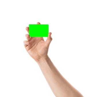 男性の手は白い背景の上のクロマキーで分離されたクレジットカードまたは名刺を保持します。