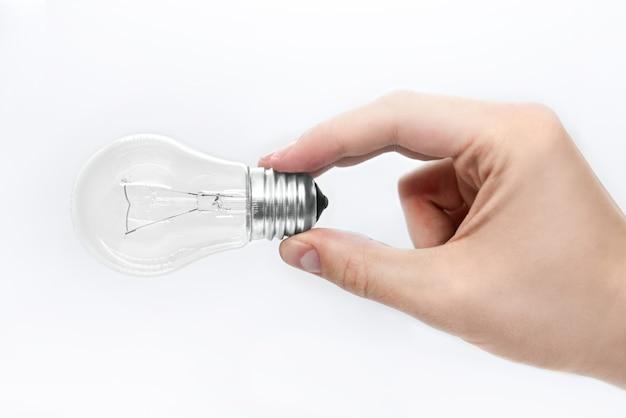 Мужская рука держит лампочку на белом фоне