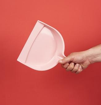 Мужская рука держит розовый пластиковый совок на красном фоне