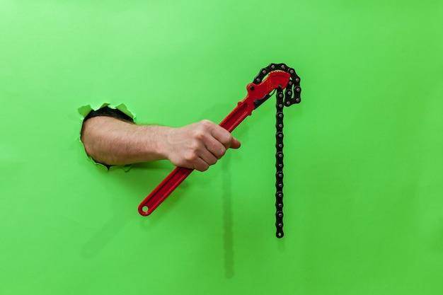 男性の手は、破れた緑の紙を通して赤いパイプの鍵を握っています。破れた緑色の紙を手渡します。テキスト、ロゴ、デザインの場所が記載された写真。コンセプトの修理とツール