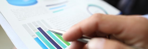 남성 손 사무실 근접 촬영에서 그래프와 차트 문서에 볼펜을 보유하고있다. 비즈니스 거래 개념의 복잡한 개발.