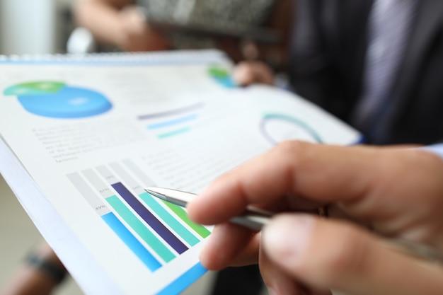 男性の手は、オフィスでグラフやチャートとドキュメントの上にボールペンを保持します