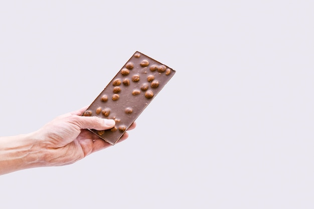 Male hand holds a bar of chocolate on gray