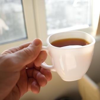 男性の手は窓の前でお茶を持っています。朝のコーヒー。ソフトフォーカスの動くアクション写真。