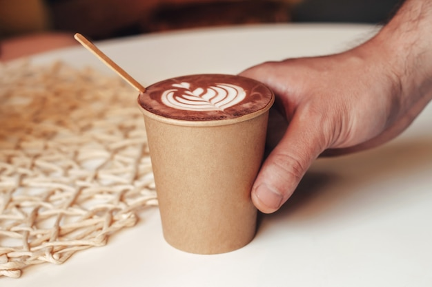 Male hand holds a disposable cup with cappuccino on a table in a cafe
