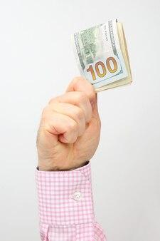 남성 손 백색 표면에 달러 지폐를 보유 프리미엄 사진