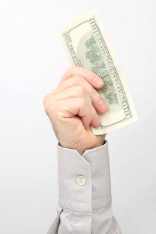 남성 손 백색 표면에 달러 지폐를 보유