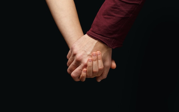 Male hand holds female hand on dark background