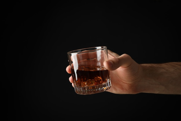 Male hand holds glass of whiskey on black background, space for text
