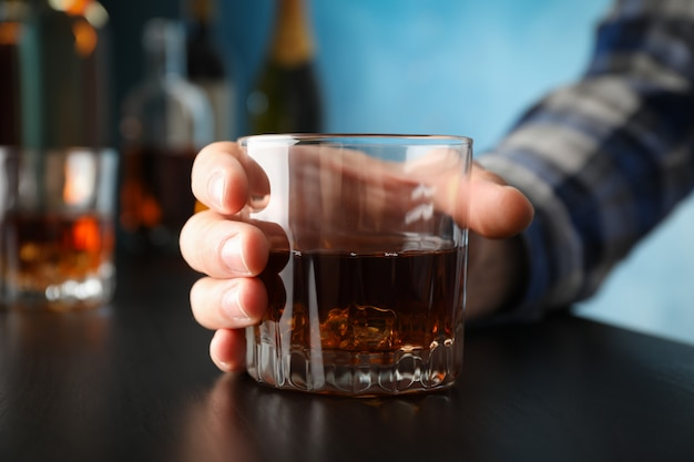 Male hand holds glass of whiskey on black table, close up