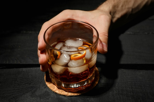 Male hand holds glass of whiskey with ice cubes on wooden background, close up