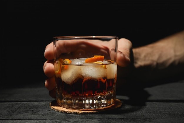 Male hand holds glass of whiskey with orange peel on wooden background, space for text