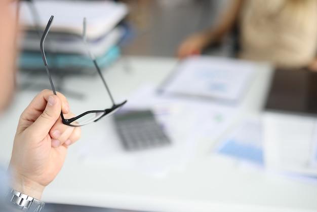 男性の手は、オフィスのデスクトップでメガネを保持しています。
