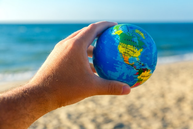 Male hand holds globe of planet earth on a seaside background. travel concept.