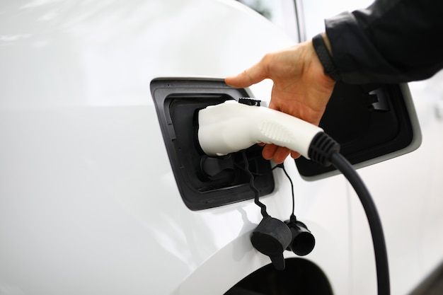 男性の手は車に充電するための挿入プラグを保持します。