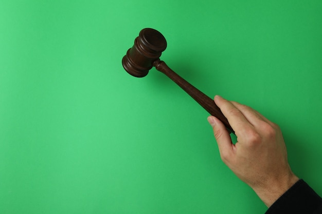 Male hand holds judge gavel on green background