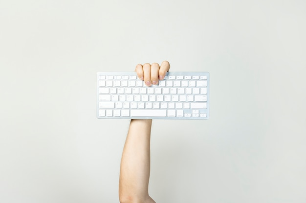 Male hand holds a keyboard on a light isolated