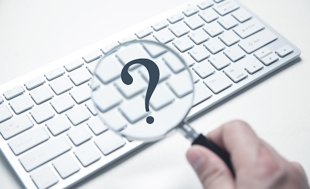 Male hand holds a magnifying glass and question mark on computer keyboard.