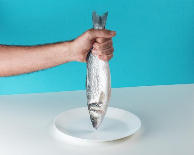 Мужская рука держит сырую свежую рыбу морского окуня