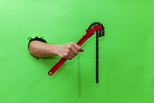 Male hand holds a red pipe key through a torn green paper. hand through torn green paper. photo with place for your text, logo and design. concept repair and tool