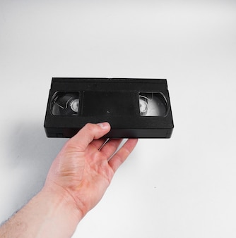 Male hand holds retro video cassette on gray surface.