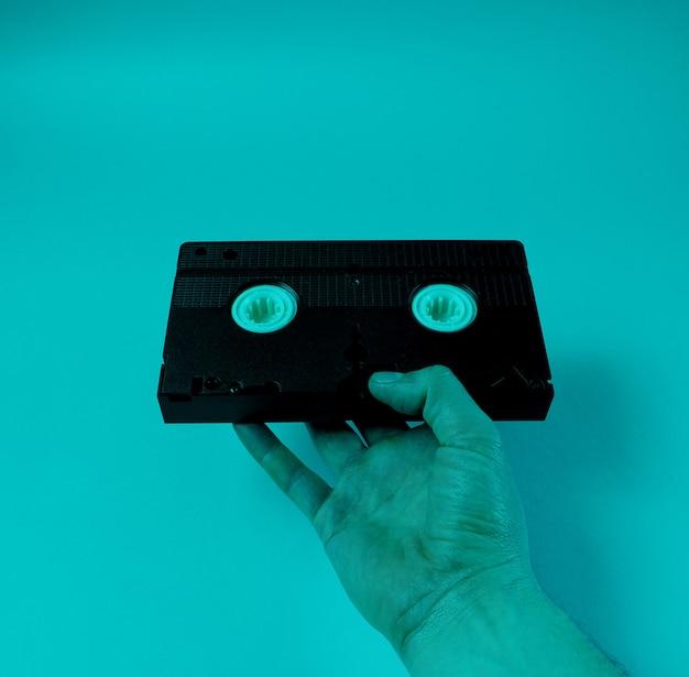 Male hand holds retro video cassette