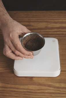 Male hand holds stainless silver cup with roasted ground coffee above the simple white weights on thick wooden table. top view