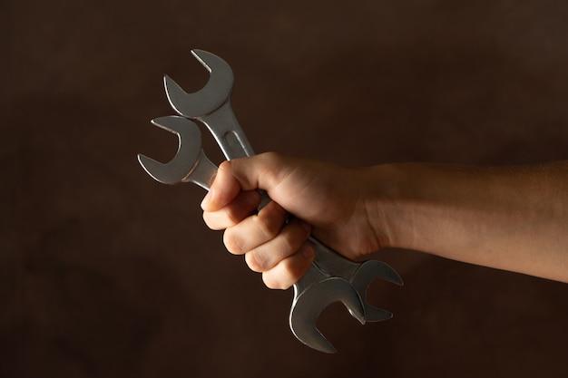 男性の手は茶色のレンチを保持します