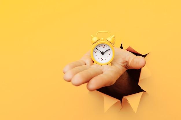 男性の手は、黄色い目覚まし時計を黄色い紙の穴に通し、時間管理と締め切りのコンセプトを持っている
