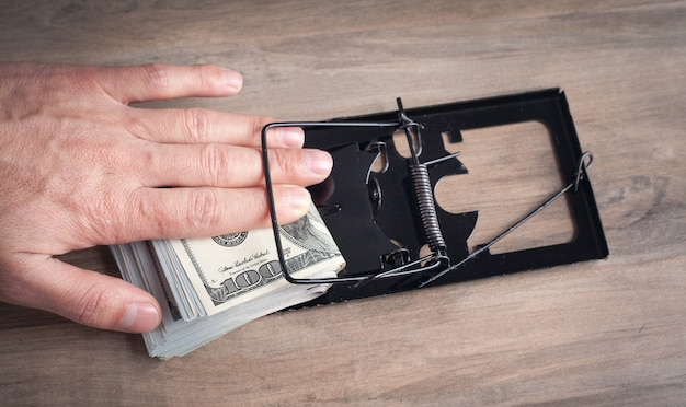 Мужская рука в мышеловке и долларах. риск