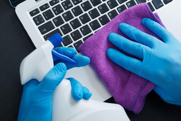 Мужская рука в синей перчатке, держащая салфетку из микрофибры и аэрозольный баллончик со стерилизующим раствором, обеспечивает чистоту ноутбука и дезинфекцию для обеспечения хорошей гигиены во время эпидемического коронавируса.