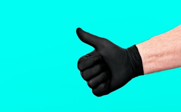 手袋をはめた男性の手、親指を上げてokサインを表示