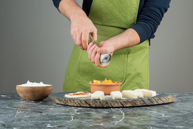 대리석 테이블에 반죽에 소금을 추가하는 장갑에 남성 손.