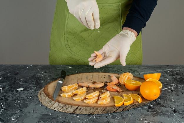 대리석 테이블에 새우에 소금을 추가하는 장갑에 남성 손.