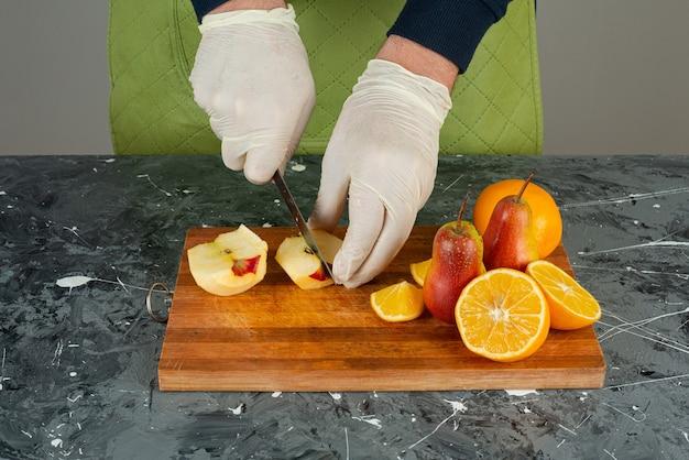 Мужская рука в перчатках, режущих свежее яблоко на мраморном столе.