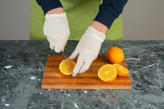 大理石のテーブルでジューシーなオレンジを切る手袋の男性の手。