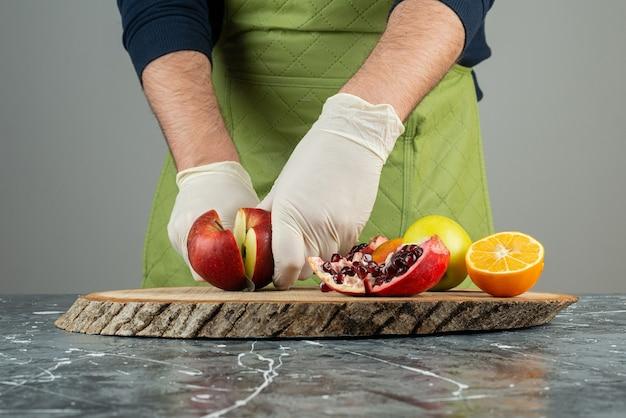 Мужская рука в перчатках, режущих красное яблоко на мраморном столе.