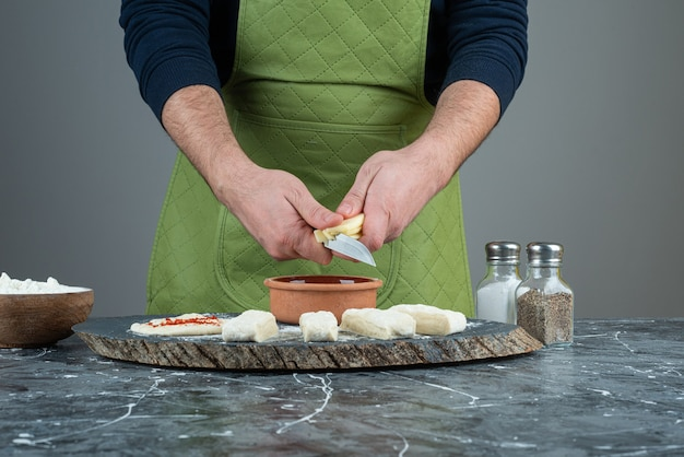 大理石のテーブルで生地を作る手袋の男性の手。 無料写真