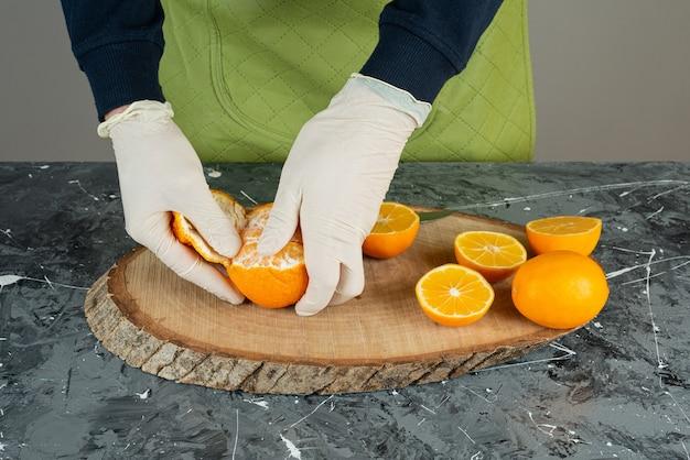 Мужская рука в перчатках, очищающих свежий мандарин на столе.