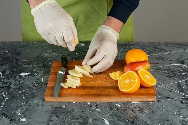 Мужская рука в перчатках, выжимая лимонный сок в яблоки на деревянной доске.