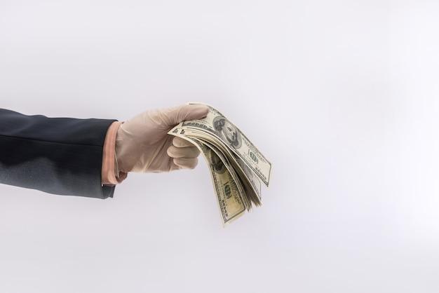 Мужская рука в медицинской перчатке держит наши денежные купюры для защиты от covid-19 (коронавируса).