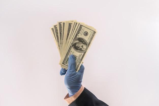 医療用手袋をはめた男性の手は、隔離されたcovid-19(コロナウイルス)に対する保護のための紙幣を持っています。