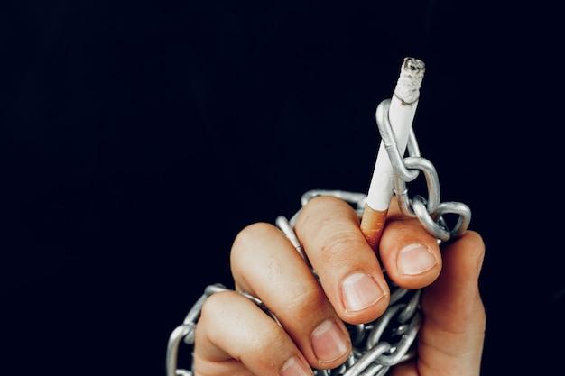 Мужская рука в металлических цепях, держащая сигарету, пристрастие к курению