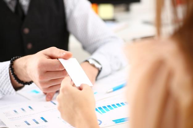 Мужская рука в костюме дает пустую визитную карточку крупным планом посетительнице